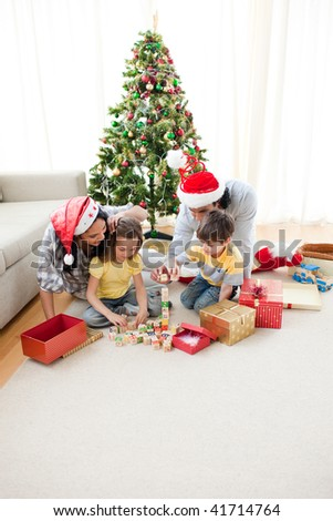 Happy family opening Christmas presents in the living-room - stock photo