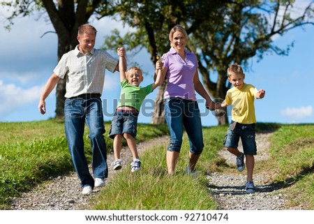 Happy family outdoors is running on a dirt path on a beautiful summer day - stock photo