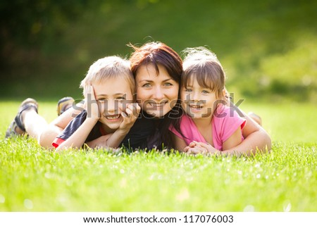 Happy family outdoors on the grass in a park, smiling faces all lying down having fun - stock photo