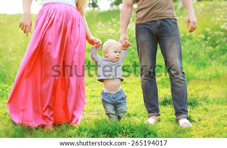 Happy family outdoors! Parents and baby on the grass in sunny summer day - stock photo