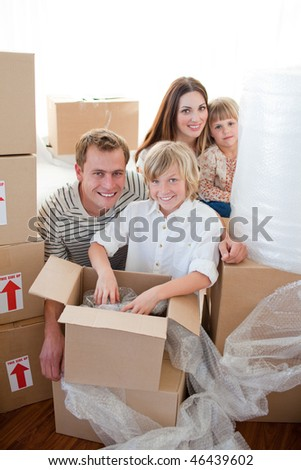 Happy family packing boxes while moving house - stock photo