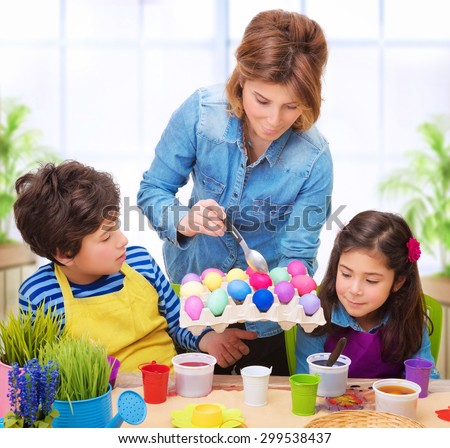 Happy family paint Easter eggs at home, mother showing her precious kids how to make traditional Easter decorative food - stock photo