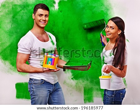 Happy family paint wall at home. - stock photo