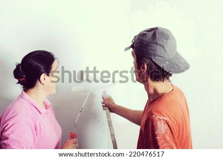Happy family paint wall at home - stock photo