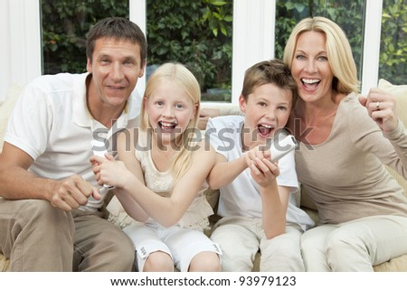 Happy family, parents, son and daughter, having fun playing video console together, the children have the remote controls, the parents are cheering. - stock photo