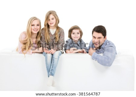 Happy family. Parents with children on the couch isolated on white background. - stock photo