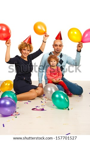 Happy family partying with balloons and confetti - stock photo