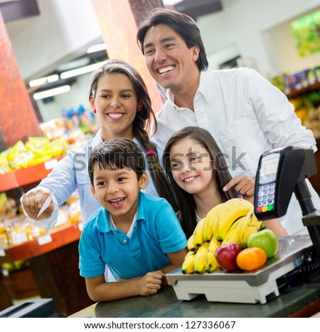 Happy family paying for groceries at the supermarket - stock photo