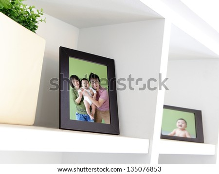 Happy Family photo on white bookshelf at home - stock photo