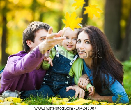 Happy family playing against blurred maple leaves background in autumn park - stock photo