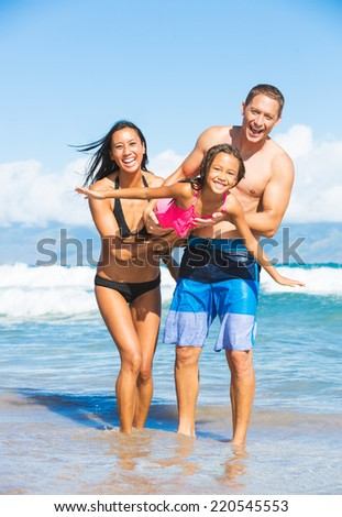 Happy Family Playing and Having Fun on the Beach - stock photo