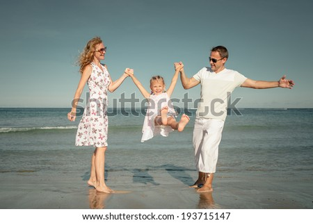 Happy family playing at the beach at the day time - stock photo