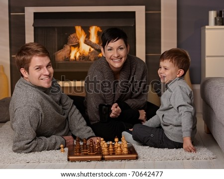 Happy family playing chess at home in a cold winter day, looking at camera, smiling.? - stock photo