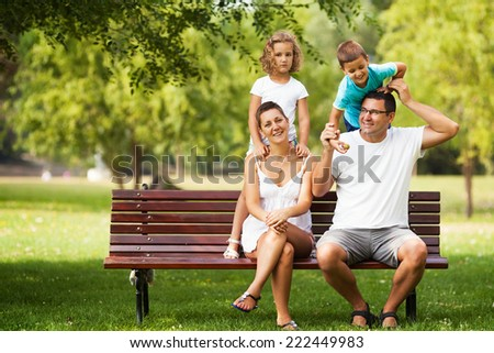 Happy family playing in a park. - stock photo