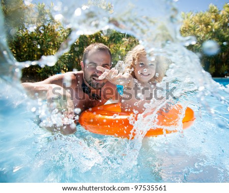 Happy family playing in blue water of swimming pool on a tropical resort at the sea. Focus on children`s hand and splash, shot was taken with waterproof box - stock photo