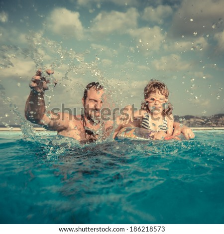 Happy family playing in swimming pool. Summer vacations concept - stock photo