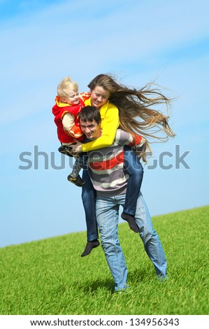 Happy family playing in the field - stock photo