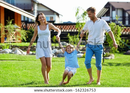 Happy family playing on a lawn - stock photo