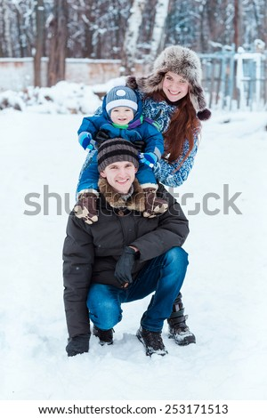 Happy family playing on snow in winter time - stock photo