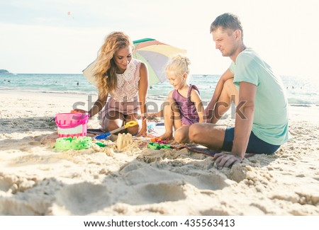 Happy family playing on the beach and build some sand castle - stock photo