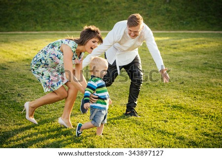 Happy family playing on the lawn in the Summer - parents catching their little son. - stock photo