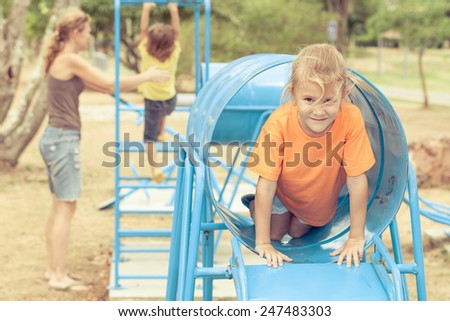 Happy family playing on the playground at the day time - stock photo