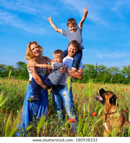 Happy family playing on the poppy meadow - stock photo