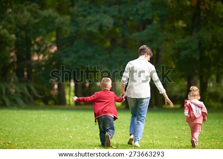 happy family playing together outdoor  in park mother with kids  running on grass - stock photo