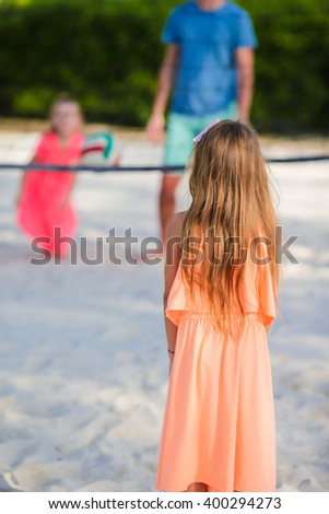 Happy family playing voleyball on the beach with ball - stock photo