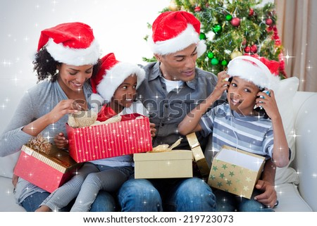 Happy family playing with Christmas presents against snow - stock photo