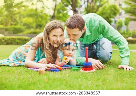 Happy family playing with their baby daughter outdoors. Girl tasting a toy - stock photo