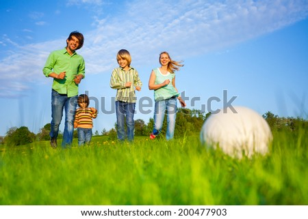 Happy family plays football in summer - stock photo