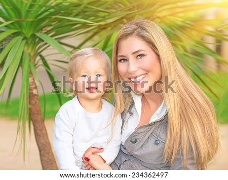 Happy family portrait, cute smiling mother holding on hands her little adorable daughter, enjoying motherhood, love and happiness concept - stock photo