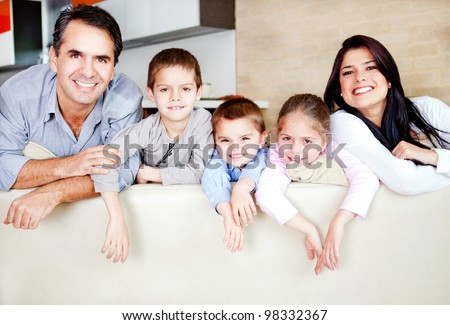 Happy family portrait leaning on the sofa and smiling - stock photo