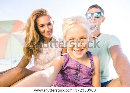 Happy family portrait on the beach. Young family on vacation taking photos - stock photo