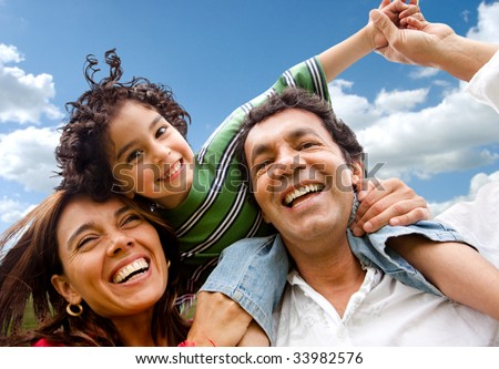 happy family portrait outdoors smiling with a blue sky - stock photo