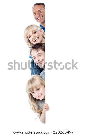 Happy family posing from behind blank whiteboard - stock photo