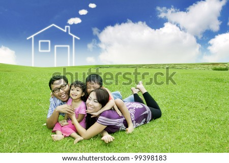 Happy family  posing on field with a drawn house in background - stock photo