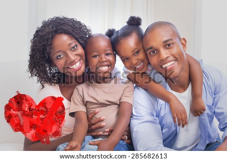 Happy family posing on the couch together against heart - stock photo