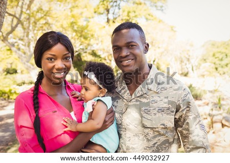 Happy family posing together at park - stock photo