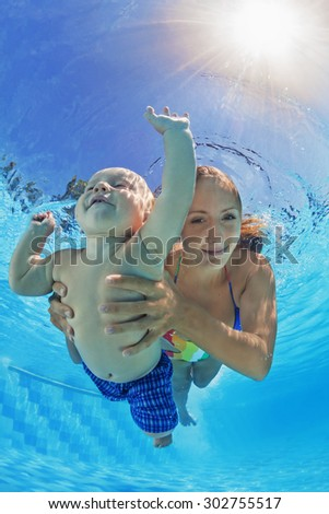 Happy family - positive mother with baby boy swim underwater and dive with fun in blue outdoor pool. Healthy lifestyle, active parents and people water sports activity on summer holidays with children - stock photo