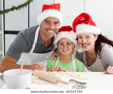 Happy family preparing Christmas cookies in the kitchen - stock photo