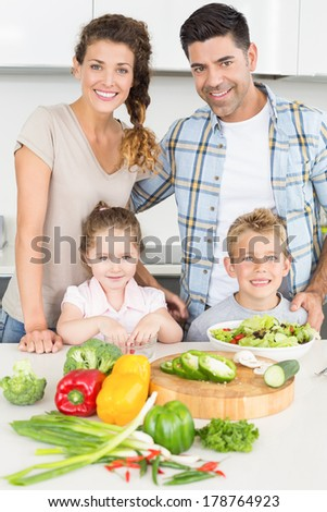 Happy family preparing vegetables together at home in kitchen - stock photo