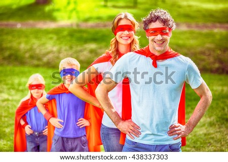 Happy family pretending to be superhero in the park - stock photo