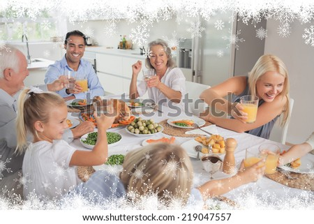 Happy family raising their glasses together against fir tree forest and snowflakes - stock photo