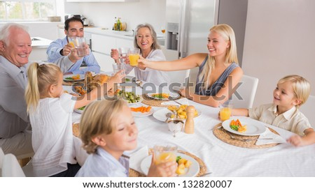 Happy family raising their glasses together for thanksgiving - stock photo