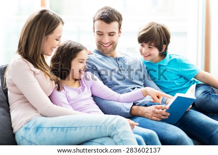 Happy family reading book together  - stock photo
