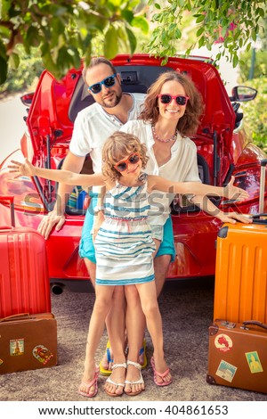 Happy family ready to trip. People standing near red car. Summer vacation and travel concept - stock photo