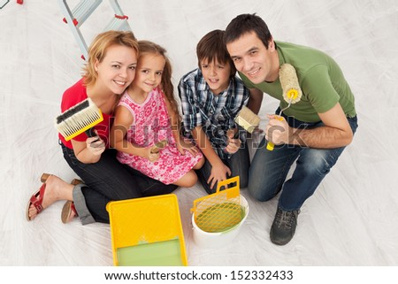 Happy family redecorating their home - sitting together with painting utensils - stock photo