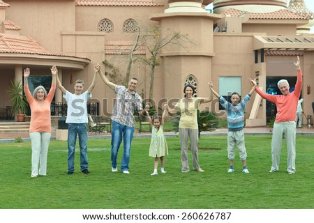 Happy family relaxing at vacation resort with hands up - stock photo
